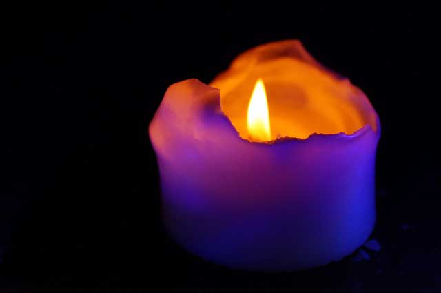 une bougie avec flamme violette